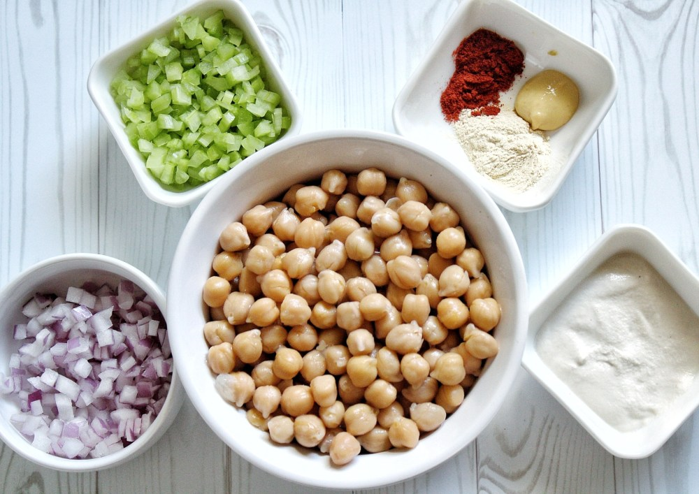 Ingredients for chickpea salad including spices, dijon mustard, cashew crea, onion, cucumber, and cooked chickpeas