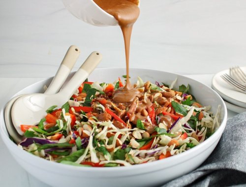 There is a almond butter dressing that's being poured over a coleslaw that's in a large shallow white bowl. There are 2 large mixing spoons in the bowl and plate plus forks in the background.