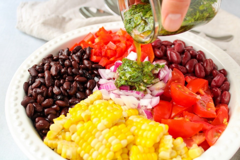 In a shallow white bowl, there are a few ingredients displayed: fresh corn, black bean, sliced cherry tomatoes, kidney beans and diced red pepper. You can see a hand holding a small jar pouring a dressing containing cilantro.
