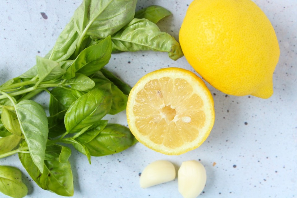 There are 2 lemon, 2 cloves of garlic and a bunch of fresh basil on a table.