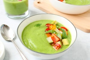 Close up on a bright green chilled soup made out of cucumber that is in a small white bowl and topped with chopped cucumber, tomatoes, avocado and basil. On the side, there is a spoon and two more bowl containing some of the soup.