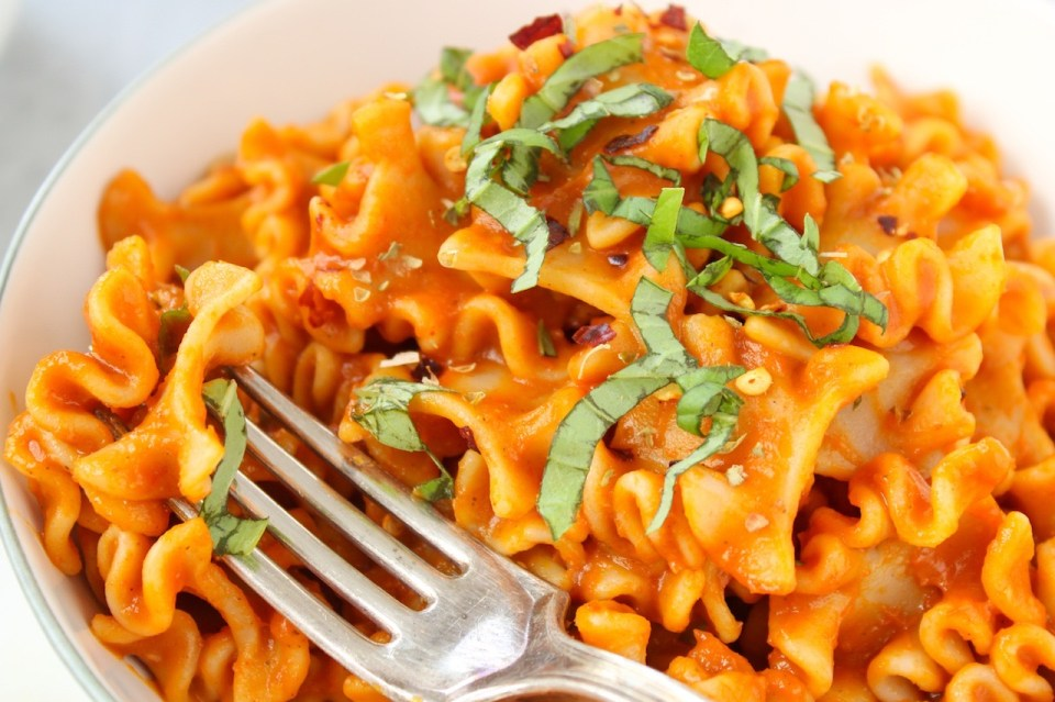 Curly short noodles cover in a red vegetable pasta sauce and topped with chopped fresh basil