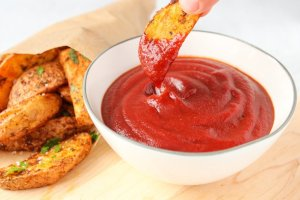 A piece of roasted potato is dipping in a white bowl containing homemade BBQ ketchup.