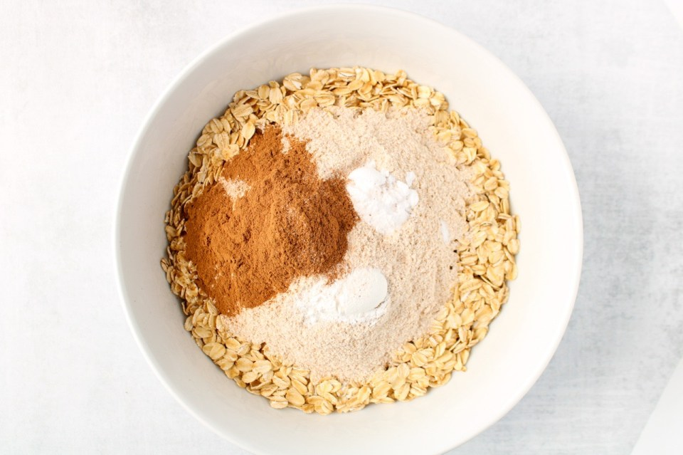 In a white bowl, you can see layered raw oats, flour, cinnamon, baking powder and soda.