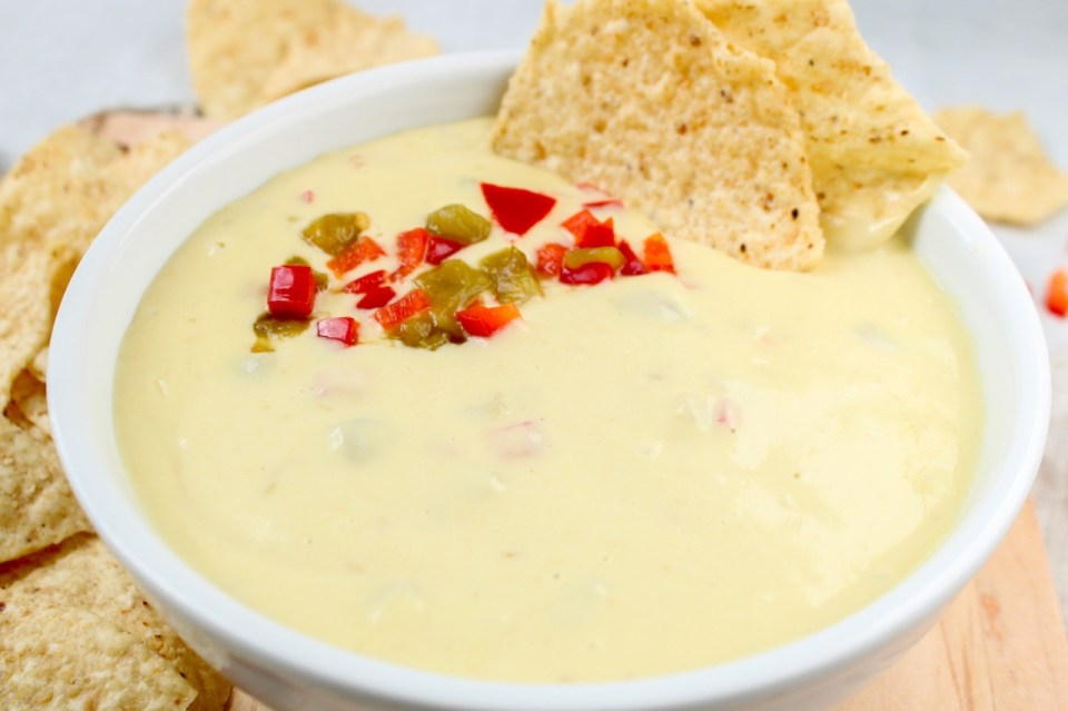 In a white bowl, there is a vegan cheese sauce topped with diced red pepper and green chiles. Also on the side of the bowl, there are 2 tortilla chips dipped in the sauce.