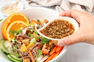 In a white bowl, you can see a mix of soba noodles with chopped cucumbers, carrots, fresh mint, green onions, oranges and roasted tofu. There is a hand holding a small bowl that is pouring a sesame soy dressing. On the table behind the salad bowl, there is a small bowl with sesame seeds.