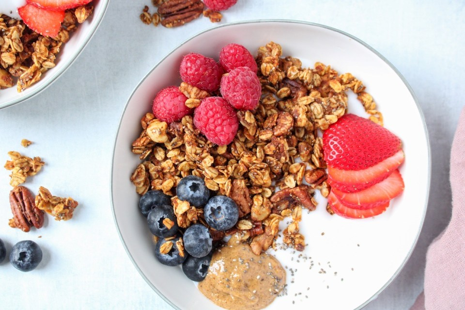 Featured is a yogourt breakfast bowl topped with berries and a homemade sweet potato granola. You can see some of the granola on the table on the side of the bowl as well as a few berries. On the side of the bowl, there is a pink hand towel.