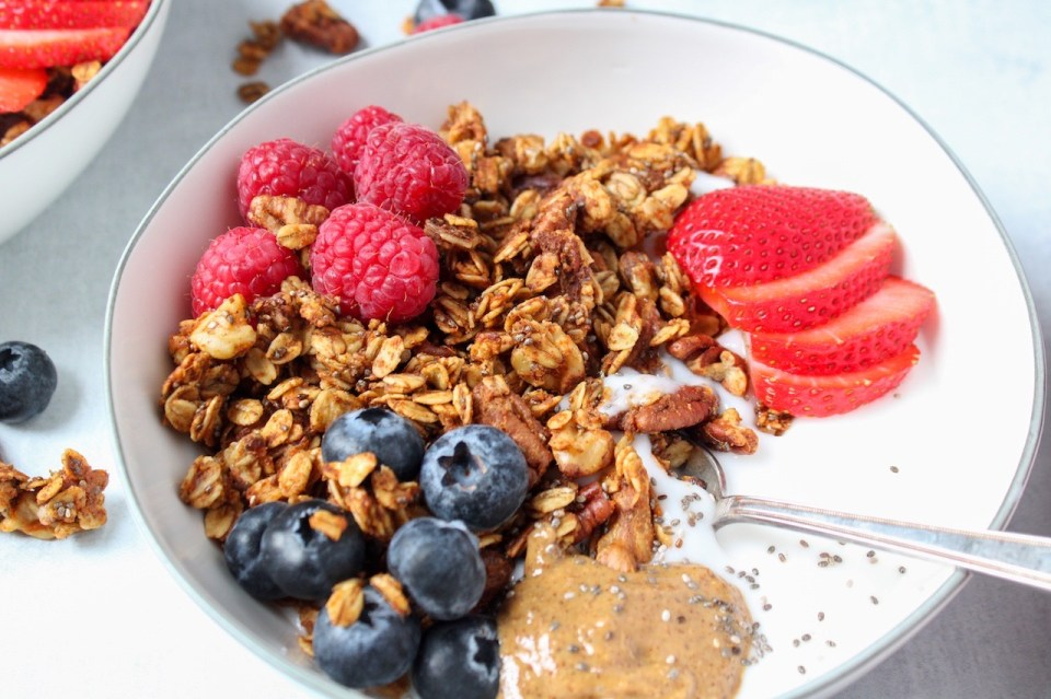 Featured is a yogourt breakfast bowl topped with berries and a homemade sweet potato granola. You can see some granola on the table on the side of the bowl as well as a few berries.