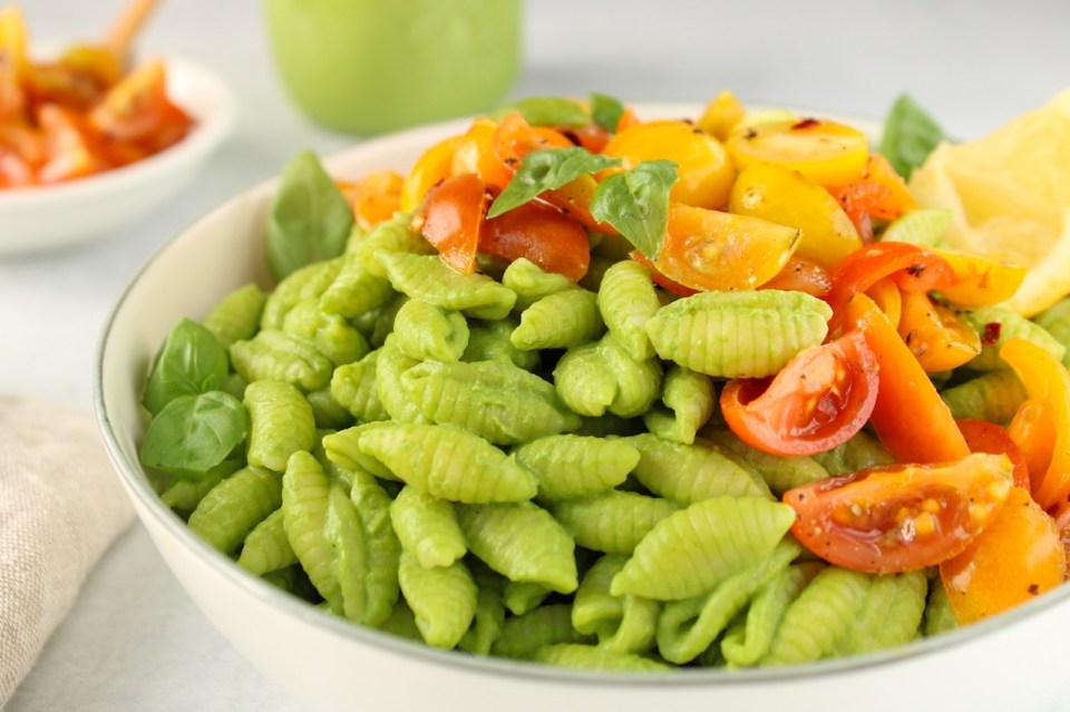 Close up on small pasta covered in a blended pesto in a white bowl and topped with chopped cherry tomatoes.