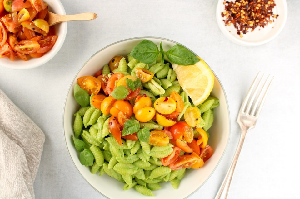 There is white bowl containing noodles covered in a creamy green sauce and topped with sliced cherry tomatoes. Also in the bowl on the side, there is a slice of lemon and fresh basil leaves. On the table, there are 2 small bowls, one with red pepper flakes and the other with sliced tomatoes.