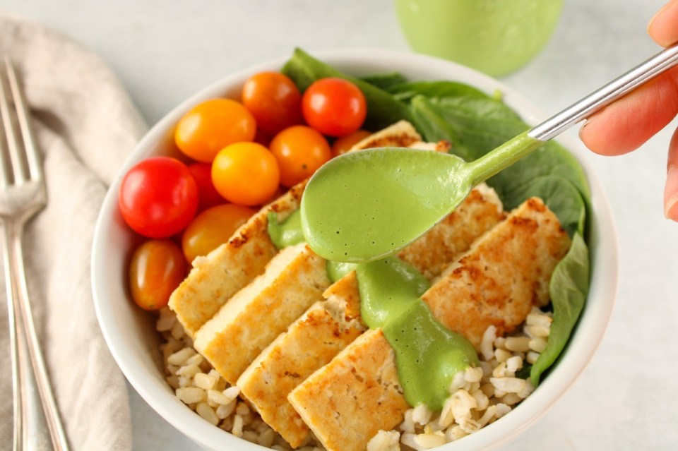 There is a spoon pouring a creamy green sauce on roasted tofu that is laying on spinach, brown rice and cherry tomatoes.