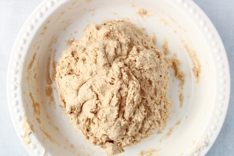 In a shallow white bowl, there is a dough for making homemade bread.