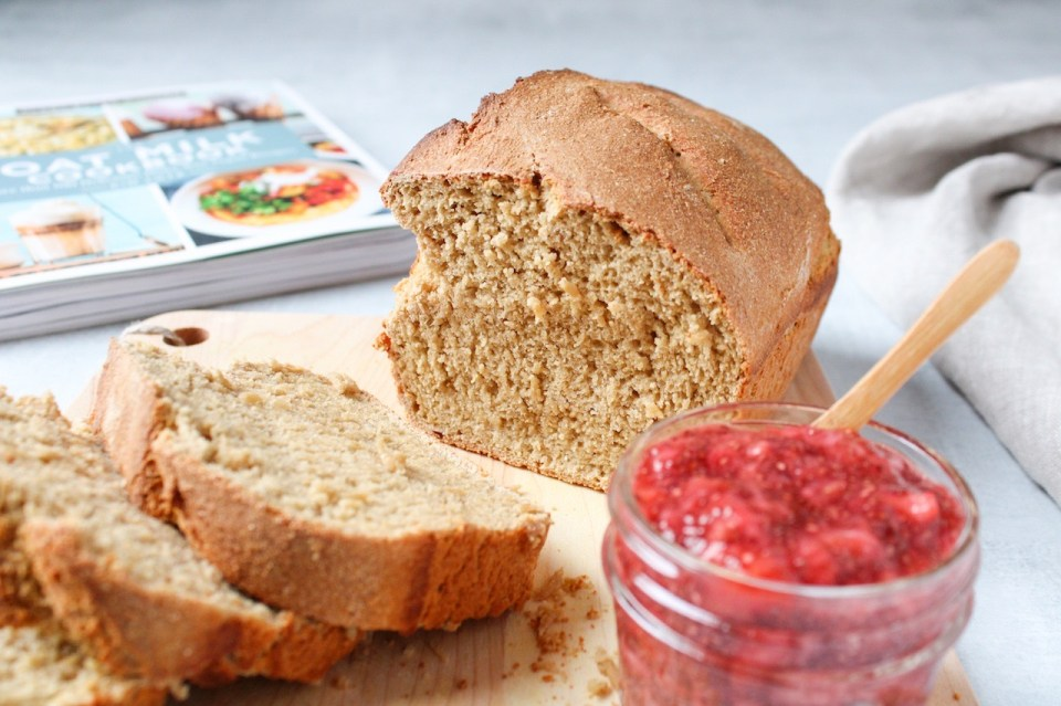 There is a Whole-Grain Oat Milk Bread with a few slices cut out of the bread displayed on a wooden cutting board. Also on the side, there is a strawberry jam in a small jar with a small wooden spoon dipped inside. In the background, you can see The Oat Milk Cookbook, where the recipe originate.