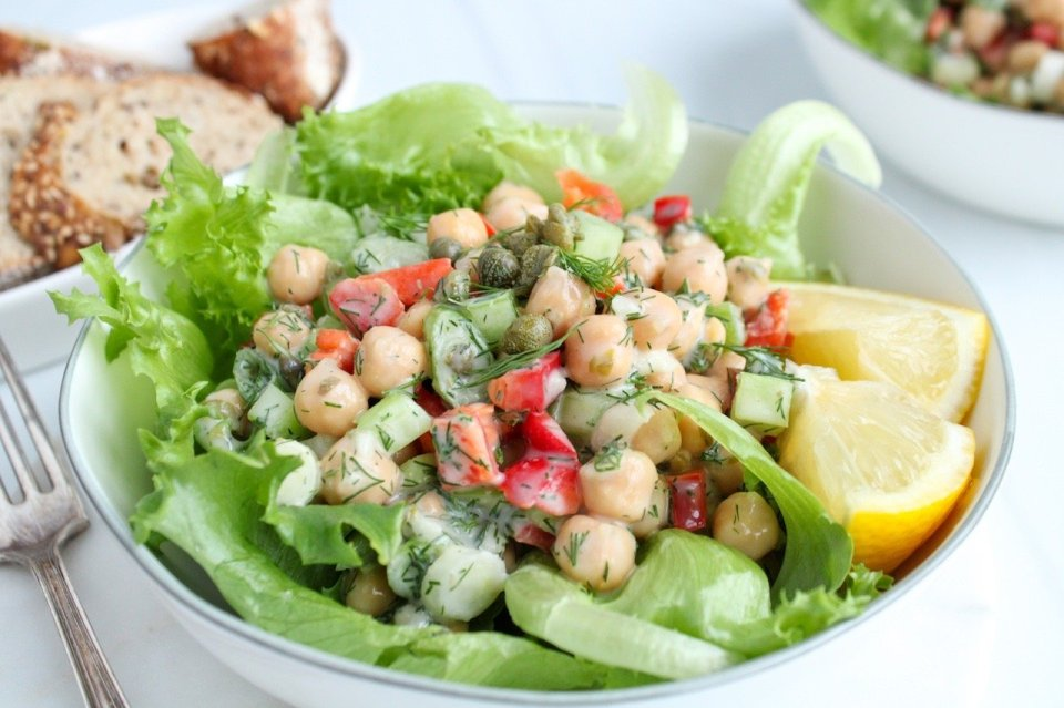 Close up on a white bowl filled with bright green lettuce and topped with a dill chickpea salad. On the side there are 2 wedges of lemon, a fork and a small bowl with sliced bread.