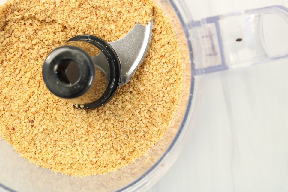 Showing is a food processor containing a yellowish crumby mixture made out of almonds, nutritional yeast, garlic powder and salt.