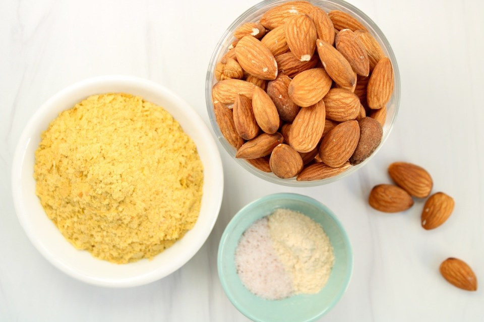 Displayed are a few ingredients in small bowls: raw almonds, nutritional yeast, garlic powder and salt.