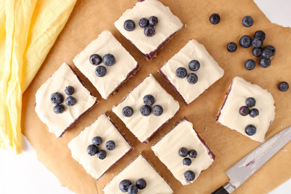 There are 9 raw vegan blueberry cheesecake squares topped with fresh blueberries and placed on a piece of parchment paper. There are more blueberries around with a knife that was used to cut the cake and a yellow hand towel.