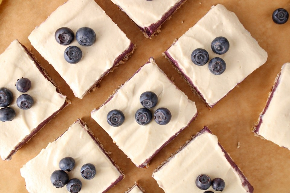 Close up with a over head shot on a few squares of raw and vegan blueberry cheesecake. The piece are topped with fresh blueberries and placed on a piece of parchment paper.