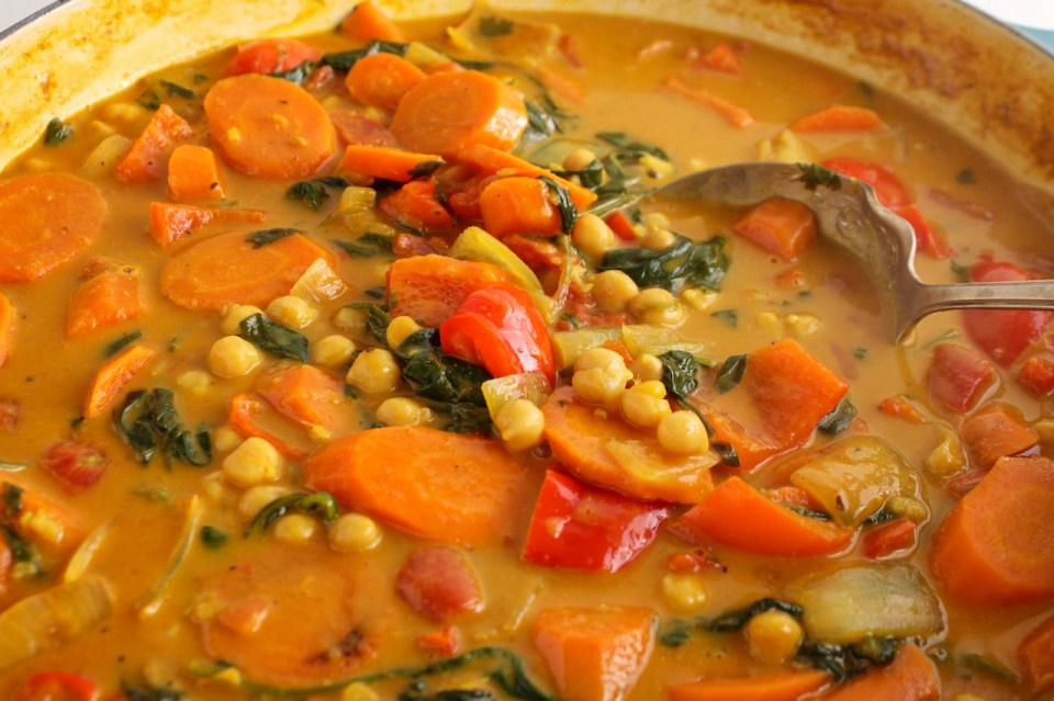 Close up on a vegetable curry stew containing carrots, red pepper, spinach, onion and chickpeas.