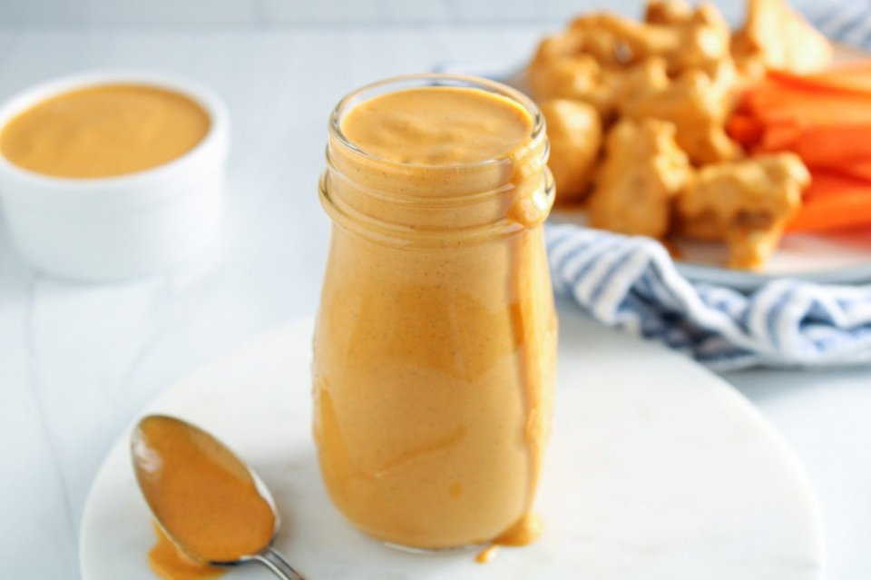 Showing is a pourable jar containing a homemade vegan buffalo sauce with a spoon covered with the sauce on the side. In the background, there is a small white bowl with more of the sauce and a white plate with cauliflower wings and sliced carrots on a white and blue hand towel.
