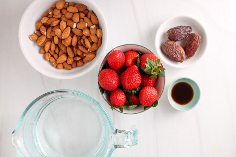 Ingredients needed to make strawberry almond milk: fresh strawberries, 3 medjool dates, vanilla extract, water and raw almonds