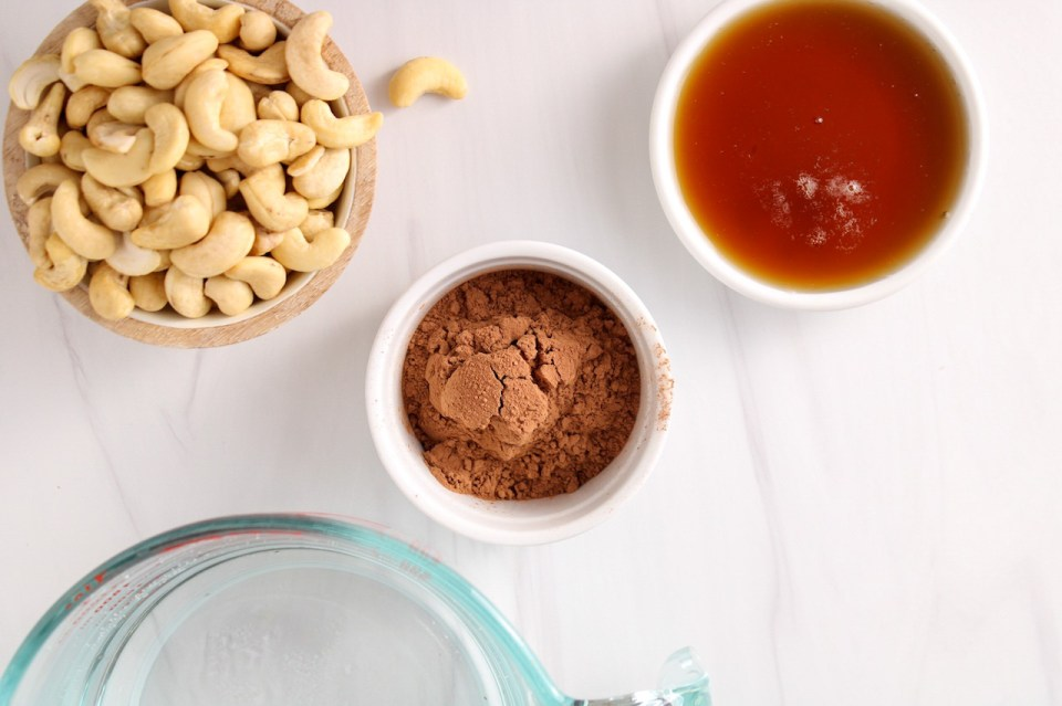 Ingredients needed to make vegan cashew chocolate milk (raw cashews, cacao powder, maple syrup and water)