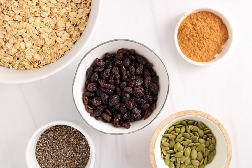 Showing are 5 small bowls containing raw oats, raisin, cinnamon, pumpkin seeds and chia seeds.