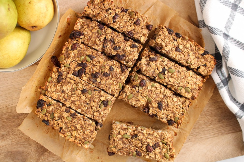 There are oatmeal raisin bars that were just sliced into bars and still on a wooden board. There is a hand towel on the side and a few pears.