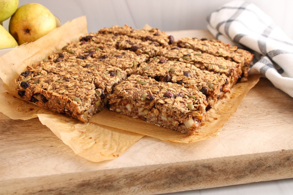 There are oatmeal raisin bars on a wooden board that were just cut into bars. There is a hand towel on the side and a few pears.