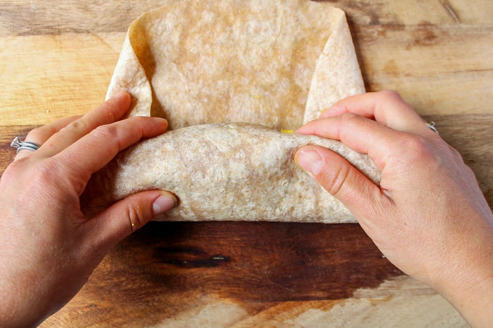 There are 2 hands holding a large burrito bread while rolling stuffing inside.