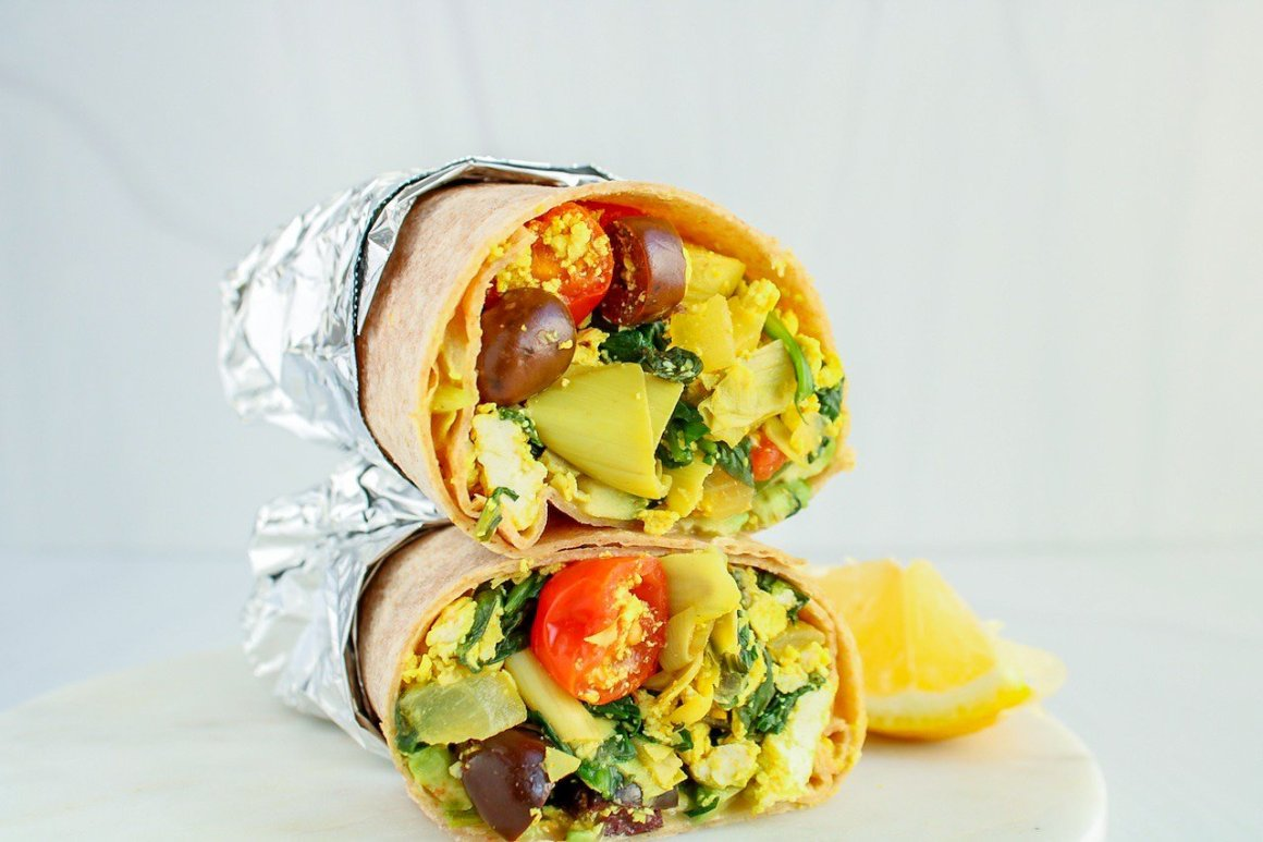 There are 2 halves tofu scramble breakfast burrito on top of each other. They are wrapped in foil and there are a few lemon wedges on the side.