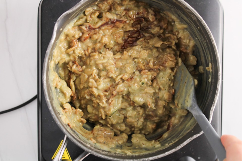 Showing is inside a small sauce pan containing green tea oatmeal with a hand stirring using a spatula.