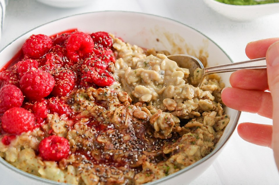 Showing is a white bowl containing a creamy matcha oatmeal topped with raspberries and chia seeds with a spoon on the side of the bowl.