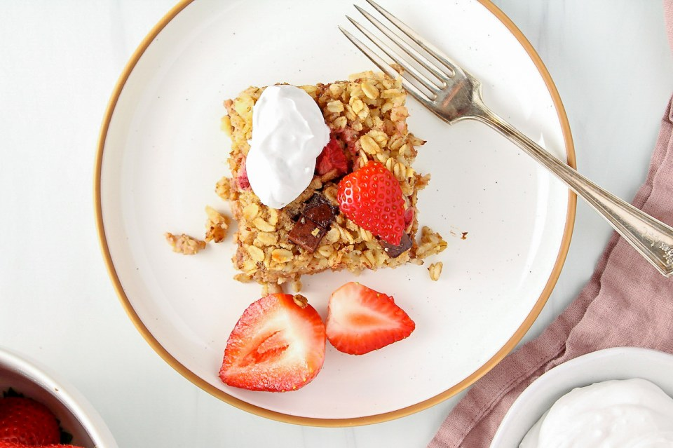 There is a square of strawberry baked oatmeal on a white plate that is topped with whipped cream and fresh strawberries. The plate is on a pink hand towel and there is a fork on the plate.