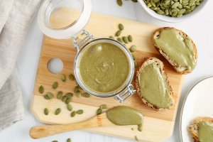 There is a homemade creamy pumpkin seed butter in a small jar with the cover opened. The jar is on a wooden board with a few raw pumpkin seeds on the side as well as 2 slices of toasts spread with some of the seed butter.