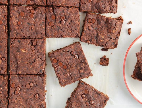 Close up on a vegan black bean brownies that was just sliced into squares. There is a small white plate with 2 pieces of brownies.