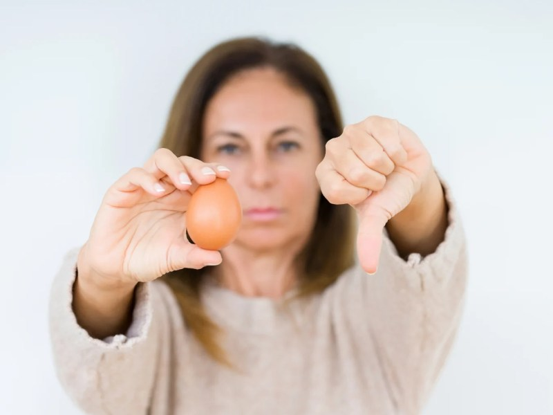 A woman holds an egg with a thumb down