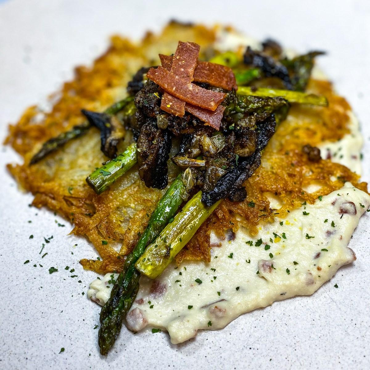 Asparagus carbonara with vegan bacon on top and piled on a creamy sauce with crispy shredded potatoes.