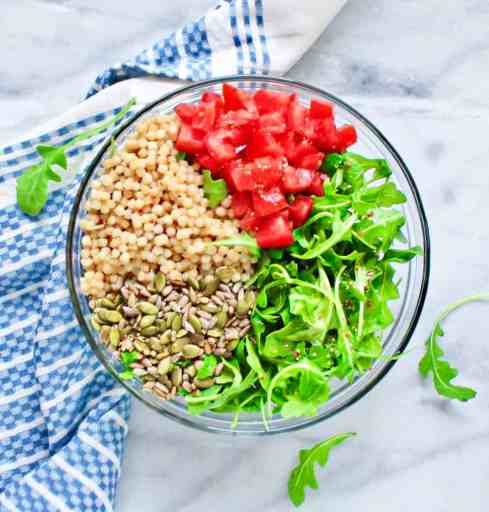 Power bowl with arugula, red tomatoes, a scoop of couscous, pepitas and sunflower seeds in a clear serving dish.
