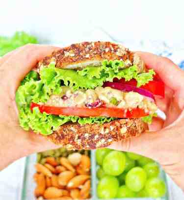 Picture of two hands holding a vegan chickpea salad sandwich with lettuce, tomato, and red onion.