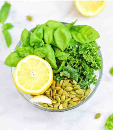 Ingredients for basil pesto. A clear bowl filled with basil, kale, pepitas, garlic, and half a lemon.