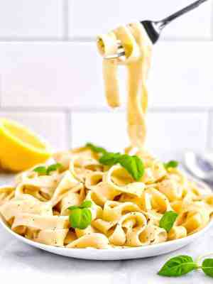 Picture of lemon pasta in a white dish, garnished with green basil leaves. Fork picking up several noodles.