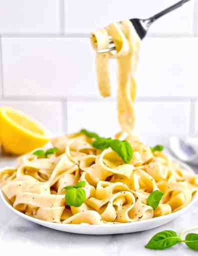 Picture of refreshing lemon pasta in a white dish, garnished with green basil leaves. Fork picking up several noodles.