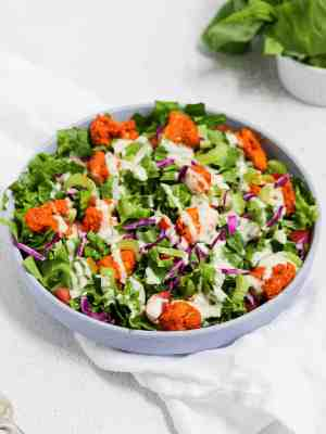 Buffalo cauliflower salad in a blue bowl with a drizzle of ranch dressing on top.