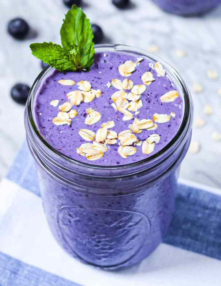 A purple smoothie garnished with green mint, uncooked oatmeal, sitting on a blue and white striped dish towel.