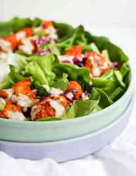 Picture of finished buffalo cauliflower lettuce wraps nestled in a green bowl which is stacked on top of a blue bowl.