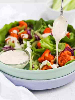 Three buffalo cauliflower lettuce wraps in a green bowl with a spoon drizzling vegan ranch dressing on top.