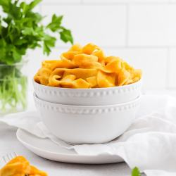 Two white bowls stacked on top of each other holding pumpkin pasta sauce with fettuccini