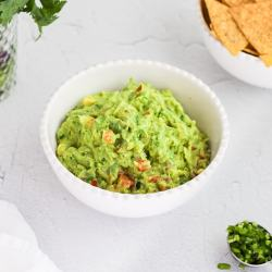 A white bowl filled with guacamole. Partially showing a bowl of tortilla chips, a cup of cilantro, and a tablespoon filled with chopped jalapeno peppers.