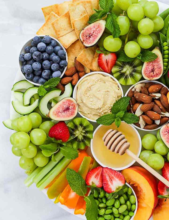 Picture of half of a snack board that is filled with hummus, nuts, fruits, and vegetables.